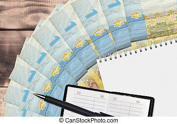 1 Ukrainian hryvnia bills fan and notepad with contact book and black pen. Concept of financial planning and business strategy
