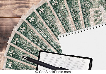 1 US dollar bills fan and notepad with contact book and black pen. Concept of financial planning and business strategy