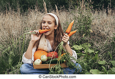 girl 11 years old sitting on the grass and eating fresh carrots, fresh apples, cucumbers, pumpkin in a basket