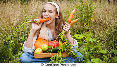 1 white girl 11 years old sitting on the grass and eating fresh carrots, fresh apples, cucumbers, pumpkin