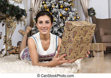 1 white girl knitted dress with gift box on white plaid near Christmas tree