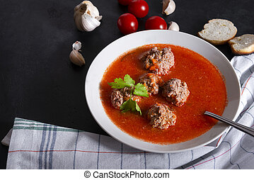 plate of red tomato soup with meatballs, garlic and cilantro on a black background, towel,