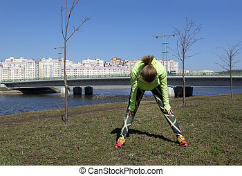 young woman in sportswear doing a workout on the street in the city by the river