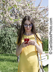 young woman with long hair in a yellow dress with a phone on the background of a blooming garden