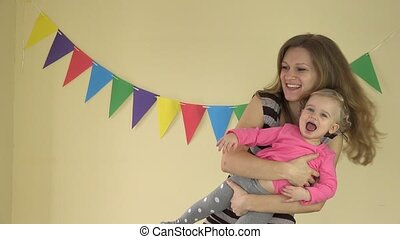1 year old baby girl dancing with mother on her hands on...