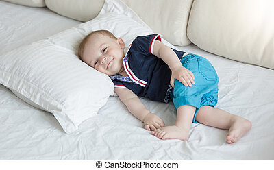 1 year old baby lying on big pillow on bed