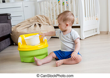10 months old baby boy learning how to use chamber pot -...