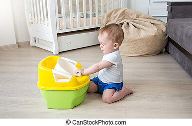 10 months old baby boy playing with baby chamber pot - 10 ...