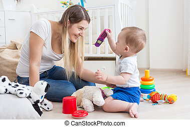 10 months old baby boy showing toy mobile phone to his mother