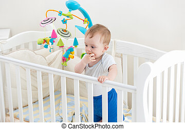 10 months old toddler boy standing in white wooden cot