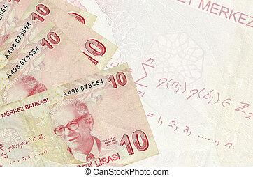 10 Turkish liras bills lies in stack on background of big semi-transparent banknote. Abstract business background with copy space