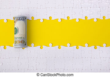 100 dollar on jigsaw puzzle pieces background