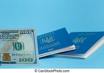 100 dollars in the front smooth, in the background 2 Ukrainian foreign passports out of focus on a blue background close-up traveling business