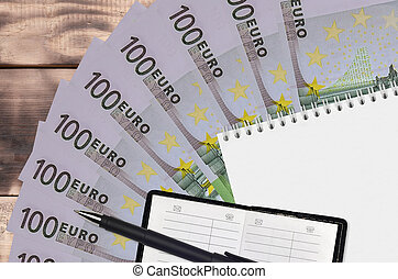 100 Euro bills fan and notepad with contact book and black pen. Concept of financial planning and business strategy