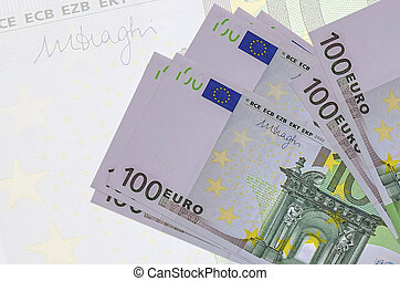 100 Euro bills lies in stack on background of big semi-transparent banknote. Abstract presentation of national currency