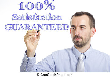 100% Satisfaction GUARANTEED - Young businessman writing blue text on transparent surface