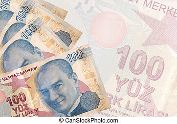 100 Turkish liras bills lies in stack on background of big semi-transparent banknote. Abstract business background with copy space