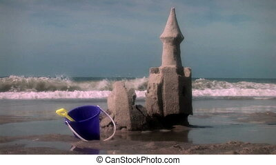 Great beach and ocean shot with sand castle in South Carolina that crumbles with the tide. Good for themes of family, vacations, summer fun, travel, whimsical, kids, storytelling, playing, meditation, irony, values, art, fantasy, etc.