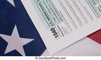 Closeup of US tax form 1040 on American flag.