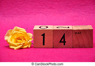 14 May on wooden blocks with a yellow rose on a pink background