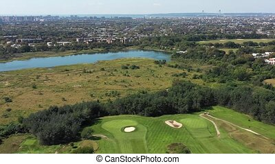 147 aerial view of golf course, city and ocean, 4k - Flying...