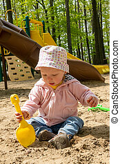 adorable blond caucasian baby playing on sand box