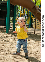 adorable blond caucasian toddler playing on sand box
