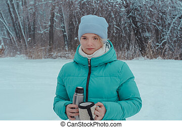 15-year-old girl walking in  winter forest holds thermos and mug of hot tea. Picnic in the snow.