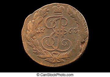 An 18th century Russian kopek isolated on a black background