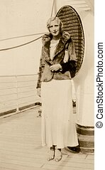 1920s WOMAN POSES ON A SHIP - A woman dressed in the style...