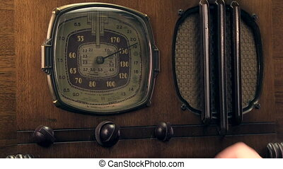 1930's vintage radio - Man's hand turning on and tuning a...
