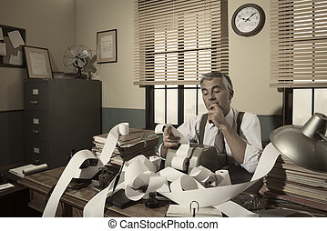 1950s accountant checking calculations in his office with...