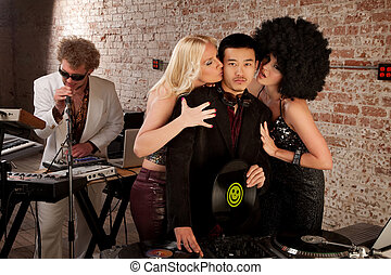 1970s Disco Music Party - Asian DJ with fangirls kissing his...