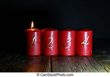 1.Advent. Red Advent candles stand on a wooden floor