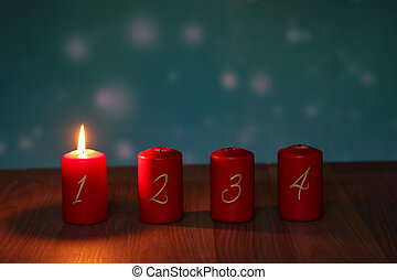 Red Advent candles stand on a wooden floor
