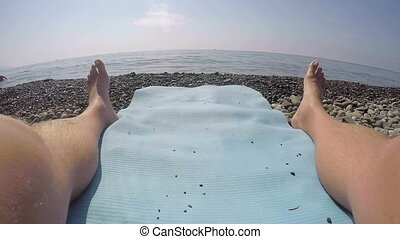 1st person POV of man relaxing on the beach mat looking...