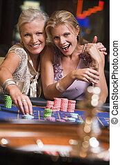 2 γυναίκα , μέσα , καζίνο , παίξιμο , ρουλέττα , και , χαμογελαστά , (selective, focus)