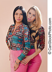 2 beautiful blonde and brunette sexy young women girl friends or sisters having fun standing together in pink leather dresses looking at camera on ivory background portrait