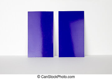 2 blank blue business cards locked on white wall, 3.5 x 2 inches size as template for design presentation, showcase etc.