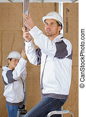 2 carpenters working indoors at construction site