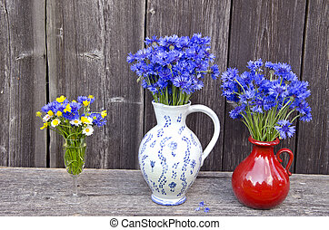 2 clay jugs and drinking glass full of cornflowers, buttercups and daisies