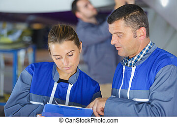 2 colleagues looking at clipboard