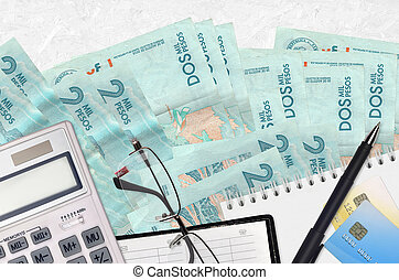 2 Colombian pesos bills and calculator with glasses and pen. Tax payment concept or investment solutions. Financial planning or accountant paperwork