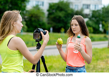 2 girls are a student. Summer in nature. Record video on the camera, for its subscribers. Concept of young bloggers, healthy eating. Hands hold an apple and bottle of water.