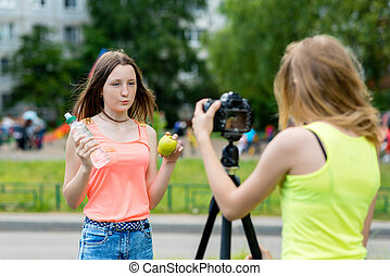 2 girls talk about fruits. Healthy brother lives a proper diet. In her hands holds bottle water and apple. Record vlog and blog subscribers. Record video lesson Internet. Use camera with tripod.