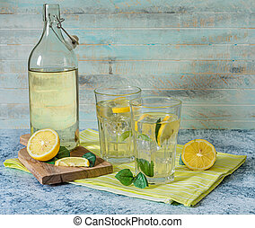 2 Glasses and bottle of fresh lemon juice with mint leaves