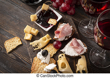 glasses of red wine , tapas, appetizer, slices of cheese, cracker, ham, jam, grapes, olives, on a dark wooden background