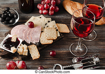 2 glasses of red wine with appetizer, bottle, slices of cheese, cracker, ham, jam, grapes, olives, baguette on a dark wooden , top view