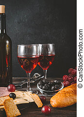 2 glasses of red wine with appetizer, bottle, slices of cheese, ham, jam, grapes, olives, baguette , cracker,  corkscrew