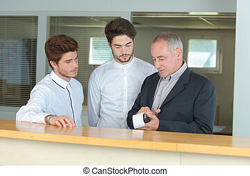 2 male students learning hotel management business with teacher